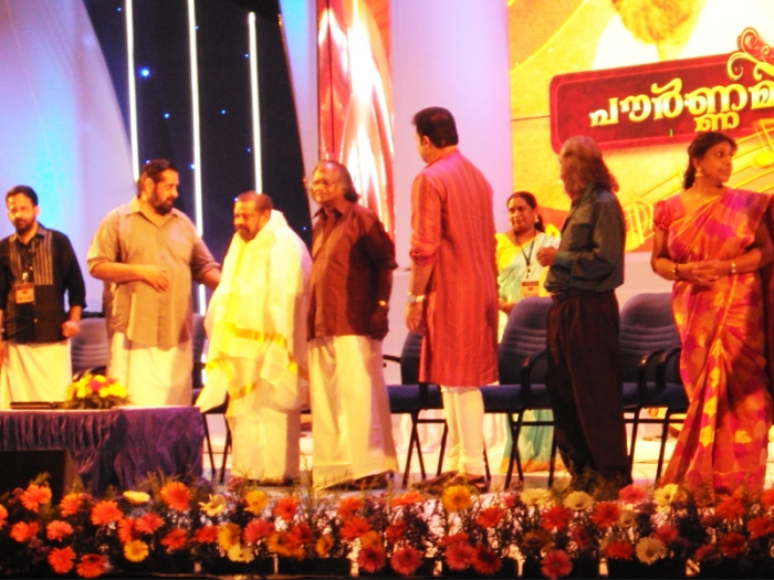 Pournamichandrika 2012 | MK Arjunan Master being felicitated wth the Traditiona Ponnaada by Madhu